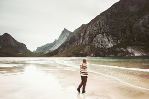 Young woman walking on wild beach