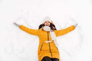 Happy playful lady lying on snow and