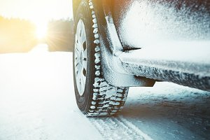 Car tire covered with snow at winter
