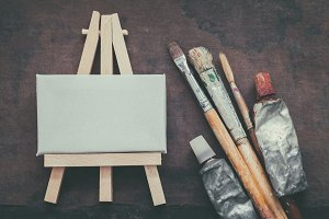 Paintbrushes, paint tubes and easel.