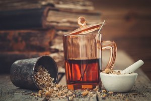 Tea glass, mortar of herbs, old book