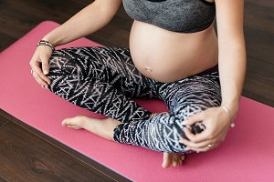 Pregnant woman cross legged on mat.