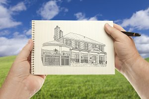 Hands Holding Sketch Pad with House