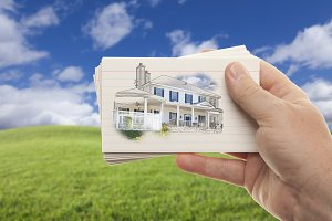 Hand Holding Cards with Drawn House