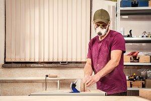 Man cuts a wooden board