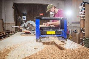 Carpenter cuts a wooden board