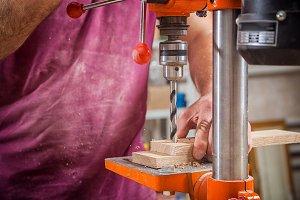 Carpenter drilling a wooden board
