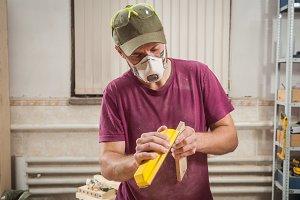 Carpenter  sanding a wooden