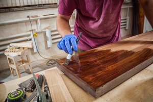 Carpenter paints a wooden board