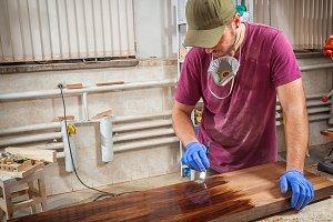 Carpenter paints a wooden board