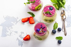 Colorful detox layered smoothie with natural edible flowers, berries and mint