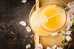 Honey in glass jar on honeycomb