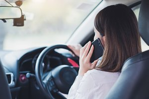 Woman using smart phone in a car