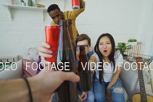Point of view shot of male hand clinking beer bottle with friends while celebrating party at home indoors