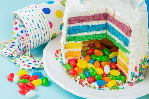 Rainbow pinata cake with candies - birthday background, card, concept
