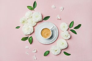 Cup of coffee surrounded with white ranunculus flowers