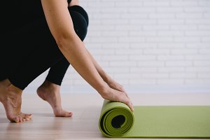 Woman rolling her green mat after a