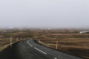 Winding road through dark Landscape