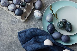 Blue Easter eggs with fluttering on plates and in a paper box