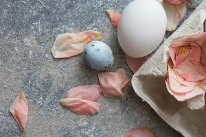 paper tray with eggs and dried rose petals on a stone background