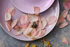 Pink plates with dried red petals on stone background