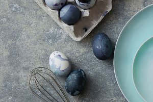 Plate with painted eggs and whisk on a concrete background