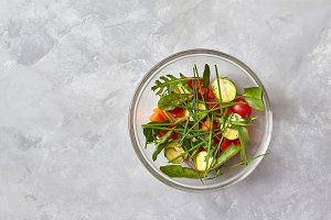 Salad from raw vegetables in a glass plate