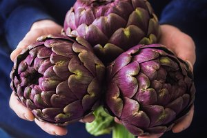 Fresh artichokes in male hands