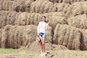 Woman posing against a stack of hay