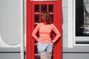 Woman posing against red phone