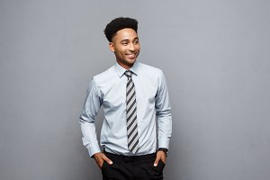Business Concept - Happy confident professional african american businessman posing over grey background