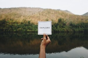 Woman holding up the word explore