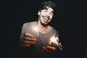 Caucasian man playing with sparklers