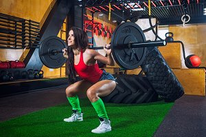 Woman doing squat  with barbell