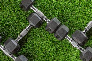 Dumbbells on green  grass