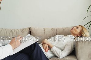 Adult woman lying on couch talking about her problems with professional male psychotherapist or psychologist in his office