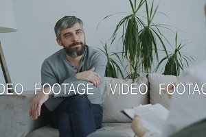 Adult bearded man sitting on couch talking to female psychotherapist in office indoors
