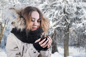 Young beautiful girl with a Cup of tea outdoors in the winter.