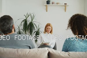 Female professional psychologist listening and writing notes in notebook while young woman arguing about boyfriend talking by phone during visit psychotherapy office indoors
