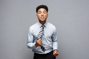 Business Concept - Angry African American with confused screaming with frustrated expression over grey background.
