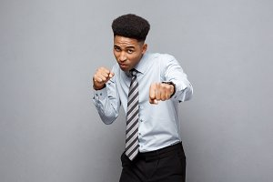 Business Concept - Confident cheerful young African American in boxing poseture over grey background.