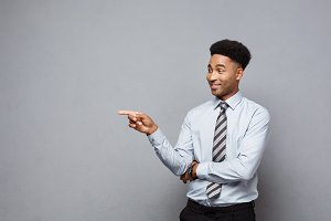 Business Concept - Confident thoughtful young African American pointing finger on side over grey background.