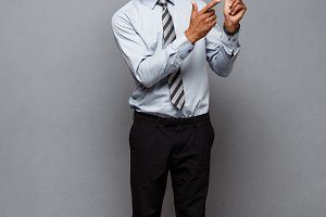 Business Concept - Full length portrait of confident african american businessman in the office pointing finger on side.