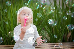 Playful Little Girl Blowing Bubbles