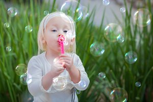 Playful Little Girl Blowing Bubbles