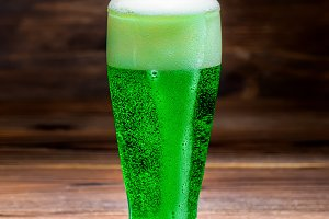 glass of green spilled foam beer