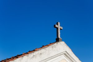 cross on the roof of the Church with orange tiles against the sky