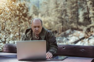 Portrait of mature man with laptop