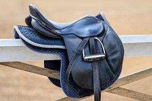 English saddle hanging on fence
