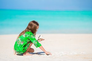 Little cute girl with seashell in hands at tropical beach. Adorable little girl playing with seashells on beach